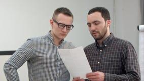读合同的两个伙伴在办公室 免版税库存图片