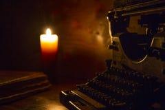 读和写场面在自古以来:一本旧书和一台老打字机在一张被破坏的木桌上由一个蜡烛点燃了在woode 免版税图库摄影