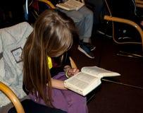 读圣经的女孩在儿童的基督徒阵营的一个教训 免版税库存照片