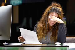 读在办公室工作区的女商人一个文件 免版税库存照片