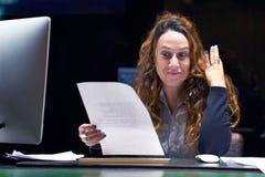 读在办公室工作区的女商人一个文件 免版税库存图片