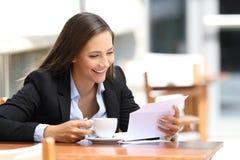 读在咖啡店的女实业家一封信 图库摄影