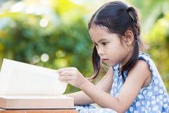 读在外部的逗人喜爱的亚裔小孩女孩一本书 免版税库存照片