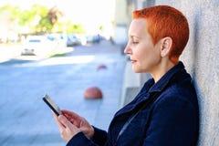 读在智能手机的女孩SMS 快乐的惊奇的情感 妇女的短的理发 时兴时髦 库存照片
