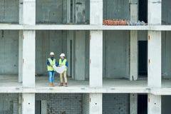 读在未完成的大厦的建筑工程师草稿 免版税库存照片
