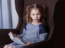 读在椅子的女孩一本书 库存照片