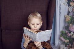 读在椅子的女孩一本书 图库摄影