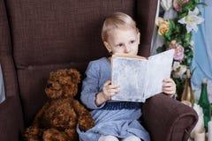 读在椅子的女孩一本书 库存图片