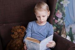 读在椅子的女孩一本书 免版税库存图片