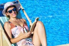 读在水池的美丽的女孩一本书完全放松了与a 免版税库存照片