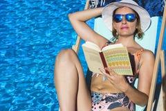 读在水池的美丽的女孩一本书完全放松了 库存图片