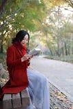 读在浪漫秋天风景的年轻亚裔肉欲的妇女一本书 相当女孩画象在秋季森林里 图库摄影