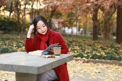 读在浪漫秋天风景的年轻亚裔肉欲的妇女一本书 相当女孩画象在秋季森林里 免版税图库摄影