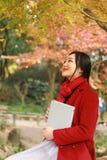 读在浪漫秋天风景的年轻亚裔肉欲的妇女一本书 相当女孩画象在秋季森林里 免版税库存图片