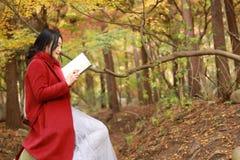 读在浪漫秋天风景的年轻亚裔肉欲的妇女一本书 相当女孩画象在秋季森林里 免版税库存照片