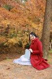 读在浪漫秋天风景的年轻亚裔肉欲的妇女一本书 相当女孩画象在秋季森林里 库存图片