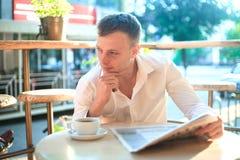 读在街道咖啡馆的体贴的人一张报纸在午餐 库存照片