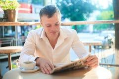 读在街道咖啡馆的体贴的人一张报纸在午餐 库存图片