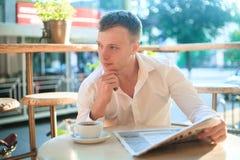 读在街道咖啡馆的体贴的人一张报纸在午餐 免版税库存图片