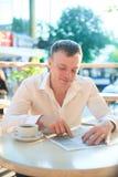 读在街道咖啡馆的Cheerfull人一张报纸在午餐 库存图片