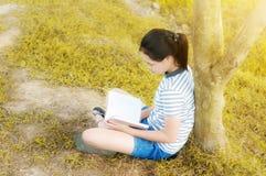 读在金草甸contryside自然的女孩一本书 图库摄影