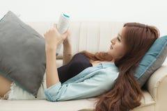 读在ebook读者的轻松的愉快的妇女一本书在家坐长沙发 库存图片