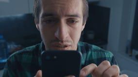 读坏消息的沮丧的人在他的智能手机 戏曲概念 股票录像
