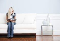读坐的沙发妇女年轻人 库存图片