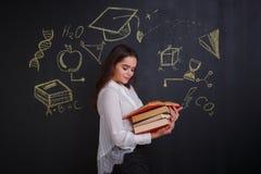 读堆书的Eoung女孩,以有科学的图片的一个委员会为背景 图库摄影