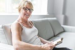 读她喜爱的小说的射击一名成熟妇女,当在家在客厅时 免版税库存图片