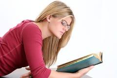 读妇女年轻人的美丽的书玻璃 免版税库存照片