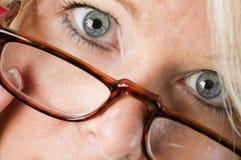 读妇女的有吸引力的白肤金发的玻璃 库存图片