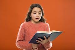 读孩子的实践 儿童文学 女孩举行书读了在橙色背景的故事 孩子喜欢读 免版税图库摄影