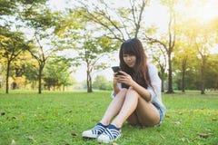 读宜人的正文消息的逗人喜爱的亚裔妇女在手机,当坐在公园春日时 库存图片