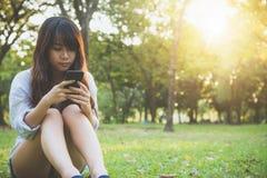 读宜人的正文消息的逗人喜爱的亚裔妇女在手机,当坐在公园春日时 免版税图库摄影