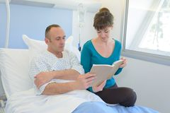 读对丈夫的有同情心的妻子在医院 免版税库存图片
