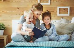 读对儿童图书的家庭母亲在床上 免版税库存图片