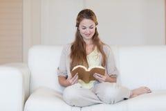 读小说的妇女在沙发 免版税库存照片