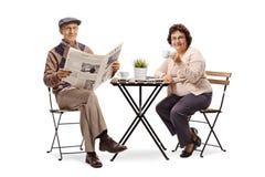 读报纸的年长人坐在与a的一张咖啡桌上 库存图片