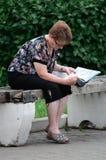读报纸的年长妇女,当坐公园长椅时 图库摄影