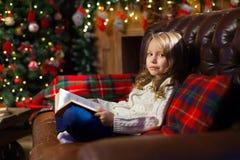 读故事书的愉快的小女孩在舒适的长沙发 免版税库存照片