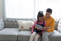 读故事书的母亲和女儿在一个沙发在客厅 免版税库存照片