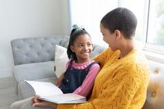 读故事书的母亲和女儿在一个沙发在客厅 图库摄影