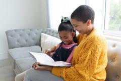 读故事书的母亲和女儿在一个沙发在客厅 库存图片