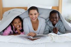 读故事书的母亲和孩子,当在家时放松在一条毯子下在卧室 免版税库存图片