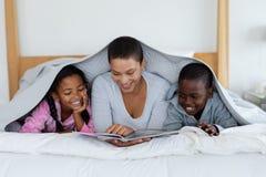 读故事书的母亲和孩子,当放松在一条毯子下在卧室时 免版税库存照片