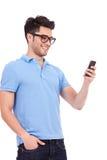 读文本的偶然人在他的电话 免版税库存照片