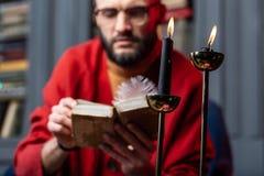 读旧书开会的有胡子的占卜者戴着眼镜在蜡烛附近 库存图片