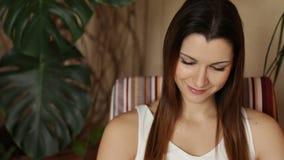 读有趣的书的年轻可爱的妇女,当坐舒适的椅子时 读书的女孩的面孔 股票录像