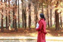 读本质上是我的爱好,女孩在公园中间散步书和 免版税图库摄影
